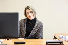 Sittigng calmo della giovane donna allo scrittorio dietro lo schermo del pc Immagini Stock Libere da Diritti