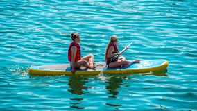 Sittiing and paddling on blue water royalty free stock photos