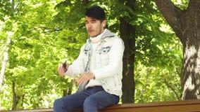 Sittin музыки студента человека слушая на стенде видеоматериал