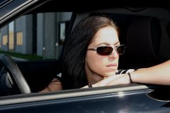Sittin in the car. Female fashion model sitting in the car waiting royalty free stock image