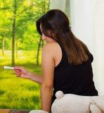 Sittin moreno bastante joven de la mujer abajo mientras que mira la prueba del hogar del embarazo, la cámara trasera del revestim Fotos de archivo libres de regalías