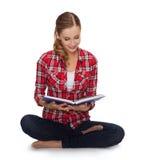 Sittin sonriente de la mujer joven en piso con el libro Fotografía de archivo
