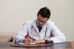 Sitting At医生签合同的办公桌 免版税图库摄影