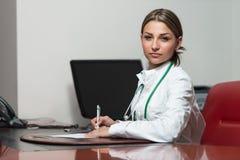 Sitting At医生签合同的办公桌 免版税库存照片