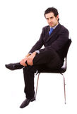 Sitting. Young businessman sitting on chair, against white background Royalty Free Stock Photo