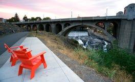 Sitting Area Chairs Riverfront View Arch Bridge Spokane Washingt. Rock falls and flowing river cuts through Spokane Washington under the Monroe Street Bridge Royalty Free Stock Photos