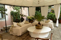 Sitting area on patio. Seating area with table under white canopy on outdoor patio in daylight stock image