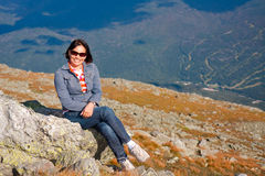 Sitting atop Mount Washington. A beautiful woman sits on rock atop Mount Washington overlooking Wildcat ski area in New Hampshire Stock Images