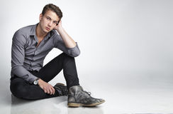 Sitting attractive young man. With head propped Stock Photography
