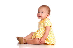 Sitting Baby. Baby Sitting and Looking Sideways Royalty Free Stock Images