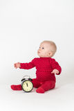 Sitting baby with clock in red suite royalty free stock images