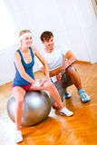 Sitting on ball slim girl and her trainer Stock Photos