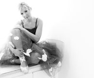 Sitting ballerina. A beautiful blonde ballerina is sitting with her legs crossed holding her ankle and looking at the viewer in this high key black and white Stock Photo