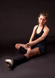 Sitting ballerina. In black ballet tutu on black background with extended leg and looking down Stock Photos