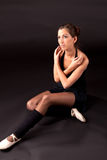 Sitting ballerina. In black ballet tutu on black background with extended leg and looking up Stock Photo