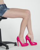 Sitting Bare Legs in Pink Heels Wearing Shorts Stock Photo