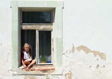 Sitting barefeet girl in a window with broken hand. Barefeet girl in red dress with broken hand sitting in the window stock image