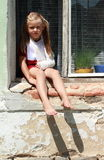 Sitting barefeet girl in a window with broken hand. Barefeet girl in red dress with broken hand sitting in the window stock photos