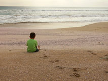 Sitting on the beach. A boy sits on a lonely, deserted beach watching the sun go down Royalty Free Stock Images