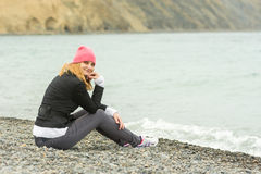 Sitting on the beach on cool cloudy day Pretty teenage girl in a pink hat Royalty Free Stock Images