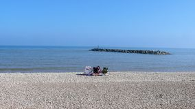 Sitting on the beach at Sidmouth royalty free stock image