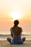 Sitting on beach at sunrise. Young woman is sitting on beach at sunrise Stock Photos