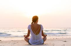 Sitting on beach at sunrise. Young woman is sitting on beach at sunrise Royalty Free Stock Photo