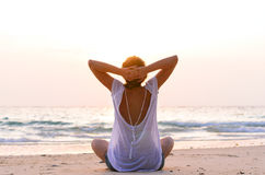 Sitting on beach at sunrise. Young woman is sitting on beach at sunrise Royalty Free Stock Photography