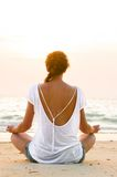 Sitting on beach at sunrise. Young woman is sitting on beach at sunrise Stock Images