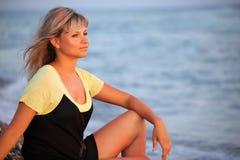 Sitting beautiful young woman on seacoast royalty free stock image