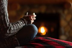 Sitting in cozy cabin by fieldstone fireplace with glass of wine. Sitting on bed in cabin with glass of wine and cozy fieldstone fireplace royalty free stock image