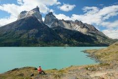 Sitting below Los Cuernos, Torres del Paine, Patagonia, Chile. Sitting below jagged peaks of Los Cuernos in Patagonia.  Orange pink jacket in front of turquoise royalty free stock image