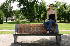 Sitting on a bench. Beautiful blond girl sitting on a bench Stock Photo