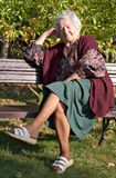 Sitting on a bench. Elderly woman sitting on a bench in the park/garden Stock Photography