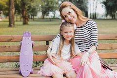 Blonde-haired mother and daughter sitting on bench in the park stock photography