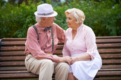 Sitting on bench. Happy seniors talking while sitting on bench in the park Royalty Free Stock Image
