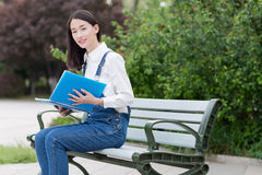 Sitting on a bench reading a book Royalty Free Stock Image