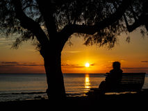 Sitting on the bench by the sea. Silhouette of a person sitting on the bench by the sea, enjoying the sunset in Novigrad, Croatia Royalty Free Stock Images