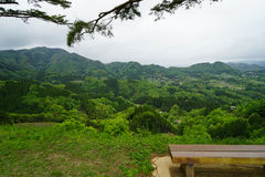 Sitting bench under big tree on hilltop with greenery mountain p. Anorama view, Takachiho, Japan Stock Image