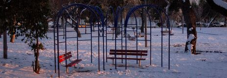 Sitting benches in the snow. A picture of sitting benches,in a snowy park,in a cold january day,in a greek town Thessaloniki Stock Image
