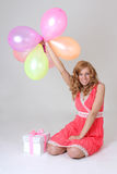 Sitting birthday girl with gift and balloons Stock Photo