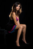 Sitting on black. Beautiful brown hair woman with sexy long legs wearing dress sitting on black background Royalty Free Stock Image