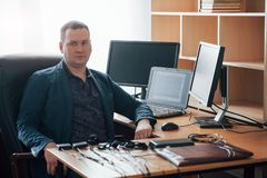 Sitting on the black chair. Polygraph examiner works in the office with his lie detector`s equipment