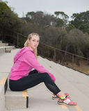 Sitting on bleachers in black tights. Blond athlete sitting on concrete steps looking right royalty free stock photos