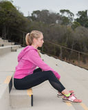 Sitting on bleachers in pink jacket. Blond athlete sitting on concrete steps looking forward royalty free stock photography