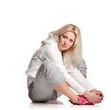 Sitting blonde fitness girl stretching. Sitting Fitness woman relax on white background Stock Photos