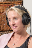 Sitting Blonde Woman at Home Wearing large Headphones and Smilin Royalty Free Stock Photo