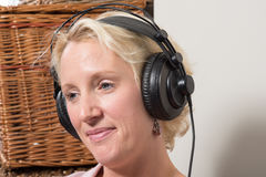 Sitting Blonde Woman wearing Headphones Tilting Head and Smiling royalty free stock photo