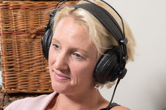 Sitting Blonde Woman wearing Headphones Tilts Head and Smiles Stock Images