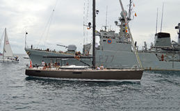 Sitting On The Boom Of Yacht By A Naval Navy Vessel  Stock Photos